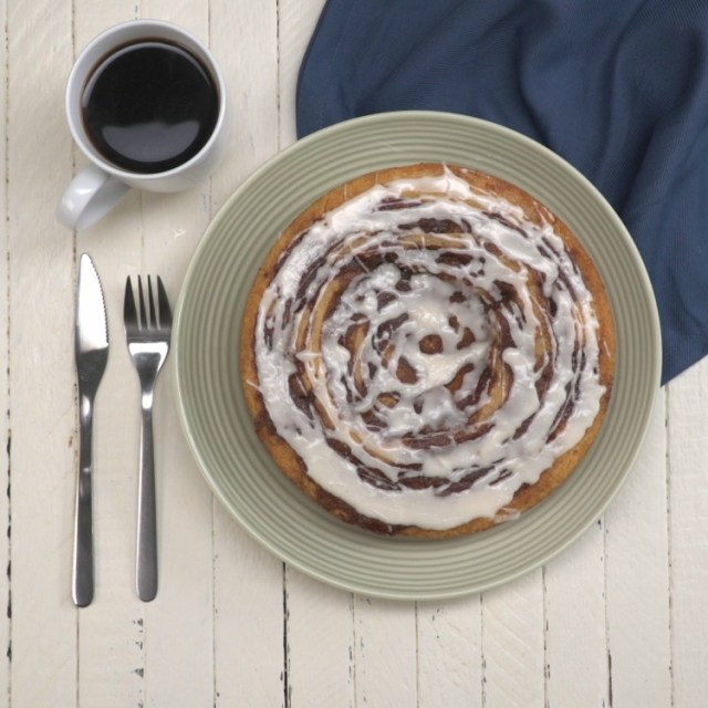 Overhead of whole cinnamon roll cake with coffee