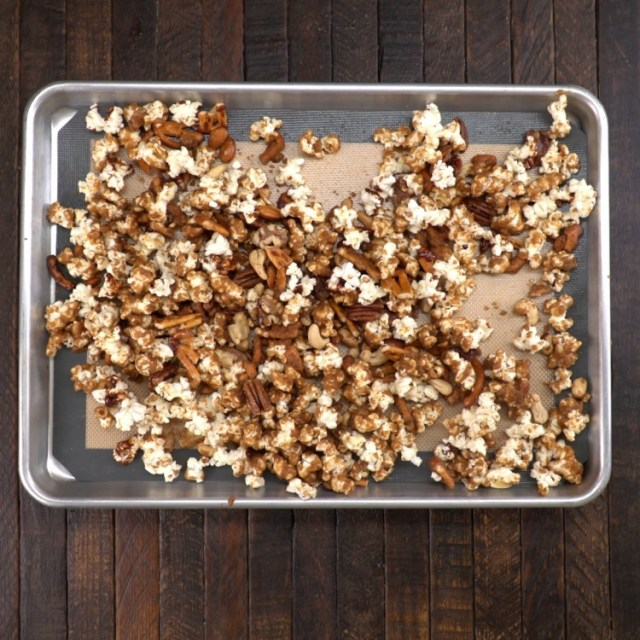To lined baking sheet. add popped popcorn, nuts, and broken pretzel twists