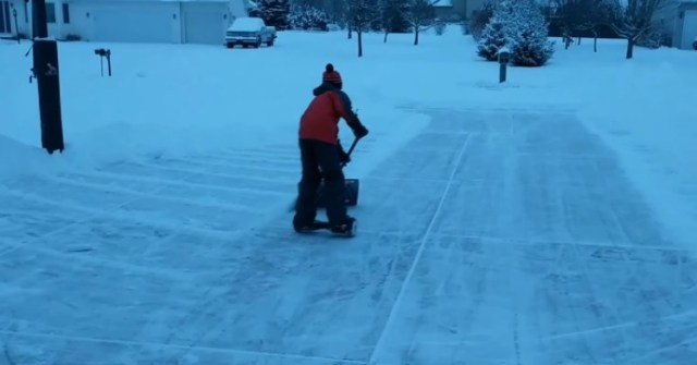 Boy uses hoverboard to shovel driveway.