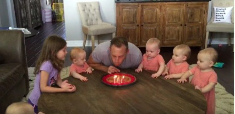 Dad blows out candles while daughters watch