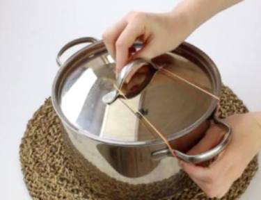 Person securing a rubber band to the top of a pot