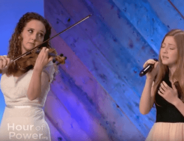 Image of violinist and young girl performing.