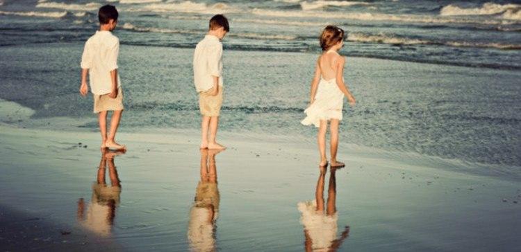 Three children on a beach.