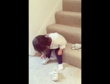 Little girl Millie putting on shoes while sitting on stairs