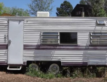 exterior view of a camper trailer in a yard