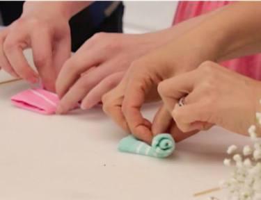 women rolling baby socks to resemble flowers