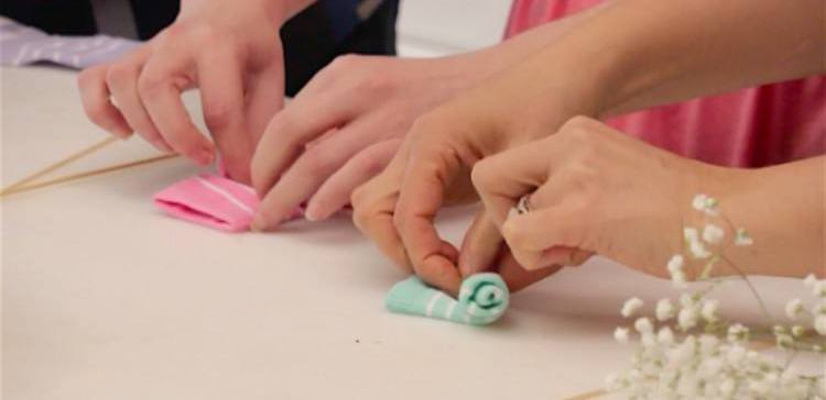 women rolling baby socks to resemble flowers