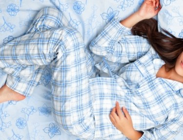 Sleeping woman in blue plaid pajamas on blue flowered sheets