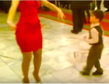 kid dances with lady in red dress