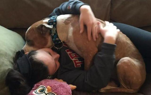 Image of girl hugging dog.