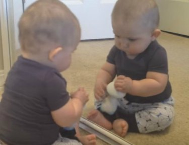 Image of baby playing with toy and mirror.