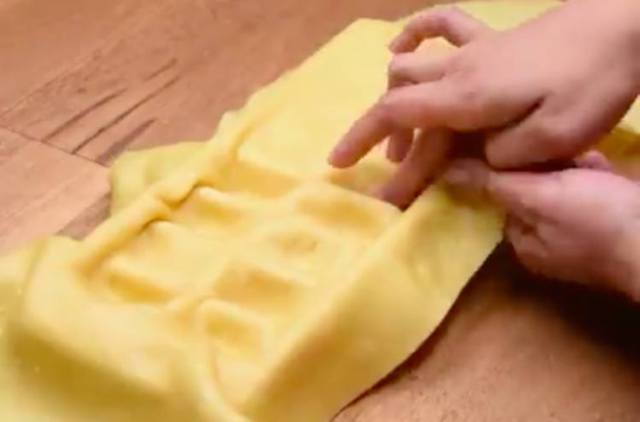 Egg pasta being draped over ice cube tray.
