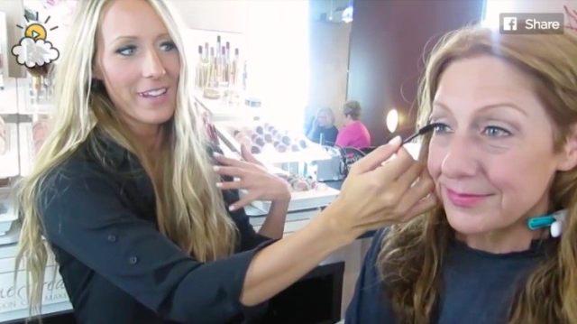 makeup artist applies color to Nancy's eyes