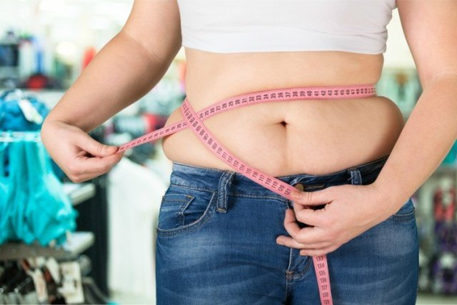 Image of woman measuring waist.