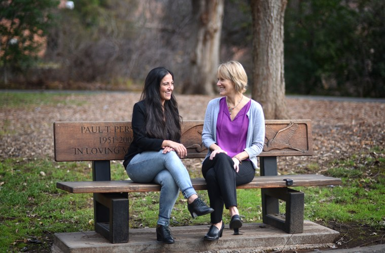 Professor Susan Roll (right) sits on a bench at CSU, Chico with her former student, Mona Kazemi (left).