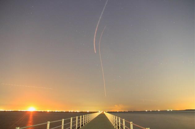 星々の間を飛ぶ飛行機の光跡