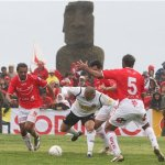 Cristian Bogado, center, of Chile's Colo Colo, fights for the ball with players of the Easter Island amateur team  Rapa Nui  during a soccer match that makes up part of the Copa Chile tournament  in Easter Island, Wednesday, Aug. 5, 2009.  (AP Photo/Marco Muga)