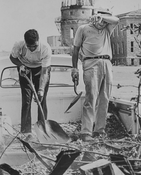 Bill Bunten, left, who was a Kansas legislator at the time of the tornado, tries to use a shovel to clean up debris at Washburn University. In the background are the skeletal remains of Crane Observatory.