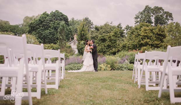 bride and groom at end of perennial border with chairs