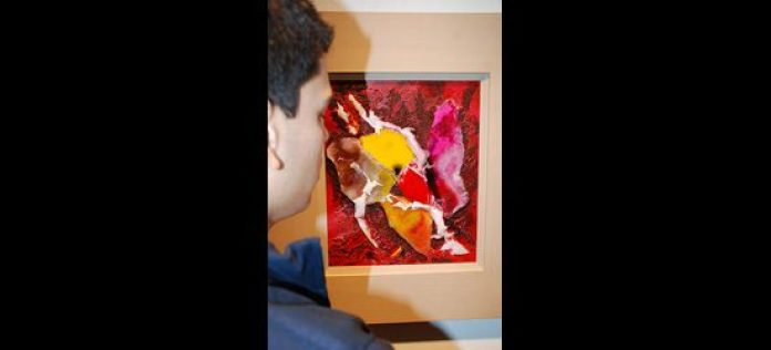 a visitor at the gallery observes the paintings at the Twelve Artists exhibition.