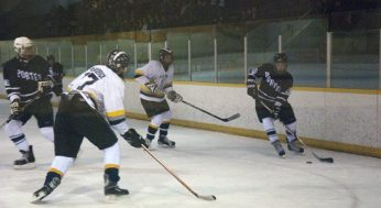 Eagles player, Eric Pashkovsky #19, tries to centre the puck. Lions player Ryan McKendrick #17 defends.
