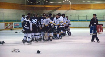 King Academy and Porter shake hands after the game. A TDSB representative waits to present the medals.