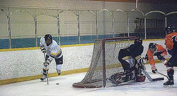 RH King Academy forward, Tyler James #9, skates out from behind the net, to give a teammate a centering pass in front. Bendale defenseman, Vinny Chiaramida #17, takes away a passing lane, and forces King Academy to the other side of the net.