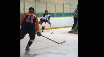 Lion, Dallas Massey #91, skates out from behind the net with the puck. Tiger, Phillip Dunaway #11, goes to challenge him.