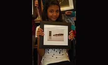"""Samantha B. holding up her photo, """"Stand Firm"""" which expresses the importance of being yourself so that you won't fall behind others."""