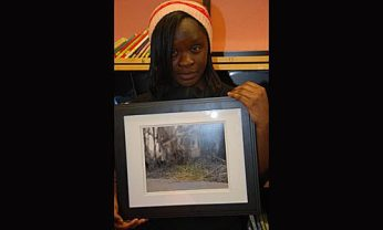 """Priscilla Y. holding her photo, """"Defy the Odds"""" which expresses the idea that there is always hope even in the worst situation."""