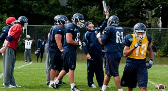 Receivers coach Cos DeMatteo instructs the offensive line for pass protection on the upcoming play.
