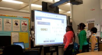 Fara Clermont scores a goal playing hang man soccer using the Smart Board.