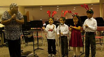 Six-year-old Raquel Romero, in the red dress, performed at the Scarborough Civic Centre tree-lighting event Dec. 1. She sang Christmas songs with three other children, led by their music instructor Jacqueline John.