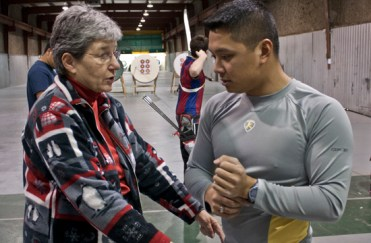 Duenas and Coach Joan McDonald, 69, discuss various exercises that can help maintain his form on the range.