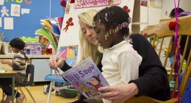 A kindergarten student gets some help reading.