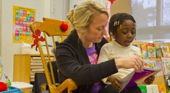 Carolyn Esau, helps one of her kindergarten students read. Esau believes full day kindergarten will give her more one on one time with each student.