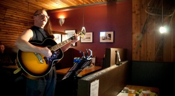 With half of his hair was cut and shaved, Larry Kosowan took a little time to play some songs on his guitar.