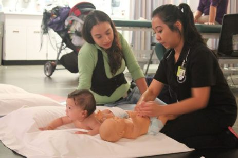 Tiffany Quintos shows Fariba Golpsand how to effectively massage her son using a doll, while baby Lyam relaxes.