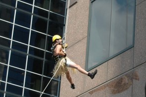Tyler Howe greets his co-workers on the second floor on Thursday as he rappels down a 17-storey building in a Hula outfit for Easter Seals Drop Zone Toronto.