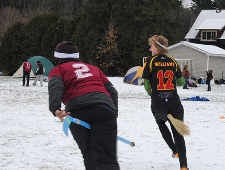 A player chases an opposing player, while both on broomsticks.