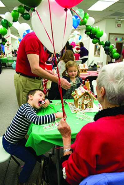 Oliver Lewis, 5, puts more candy in his mouth than on the gingerbread house he's decorating with his sister and grandparents at Habitat for Humanity's Dec. 8 Gingerbread Build. 'They're eating more candy (than decorating),' grandmother Tillie Lewis said.