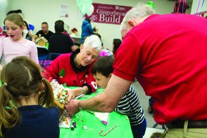 Tillie Lewis, centre, and her husband David, right, decorate a gingerbread house with their grandchildren Amelia, 3, front left, and Oliver, 5.