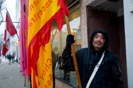 Construction worker Gordy Leong puts aside his hard hat for a different role Saturday: the group's flag-bearer. Despite the snow and rain, he was all smiles as he carried a flagpole almost twice his height and trudged on through the slush, leading the group to each store along Spadina Avenue. Leong said it takes them over four hours to complete their journey through Chinatown.