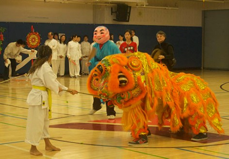 A volunteer holds out lettuce for the orange dragon and its dancer.