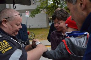 A paramedic entertains a child at the Don Mills Street Festival.