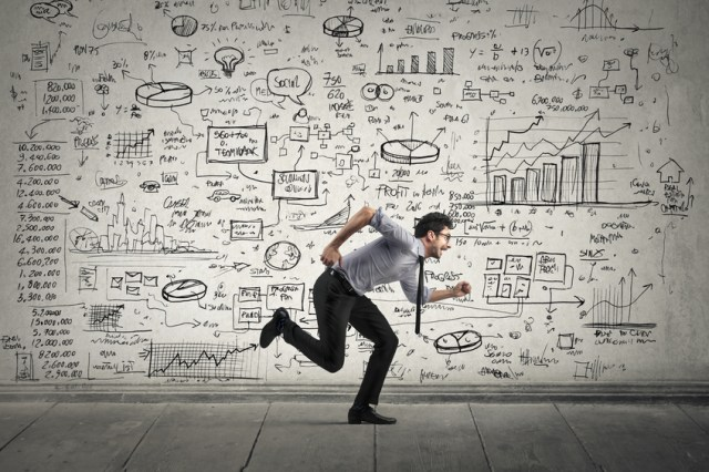 Young businessman running in front of a wall with diagrams and data written on it.