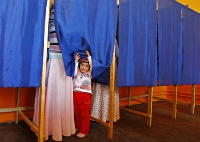 A Romanian Roma child looks out from a voting booth at a polling station in Sintesti, near Bucharest