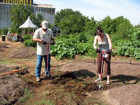 Farmer Joe gives Maddalena Romano a lesson in weeding.