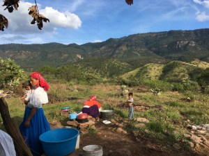 Huichol women clean up in an open-air kitchen at the new encampment in Huajimic, La Yesca. (Nelson Denman photo)