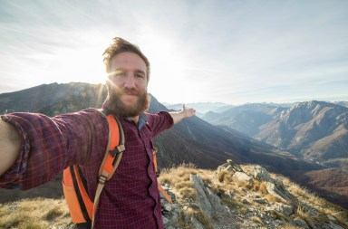 Young man hiking reaches mountain top and takes a selfie portrait with the mountain landscape on the background.